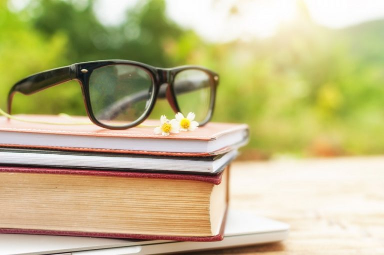 eyeglasses on top of books
